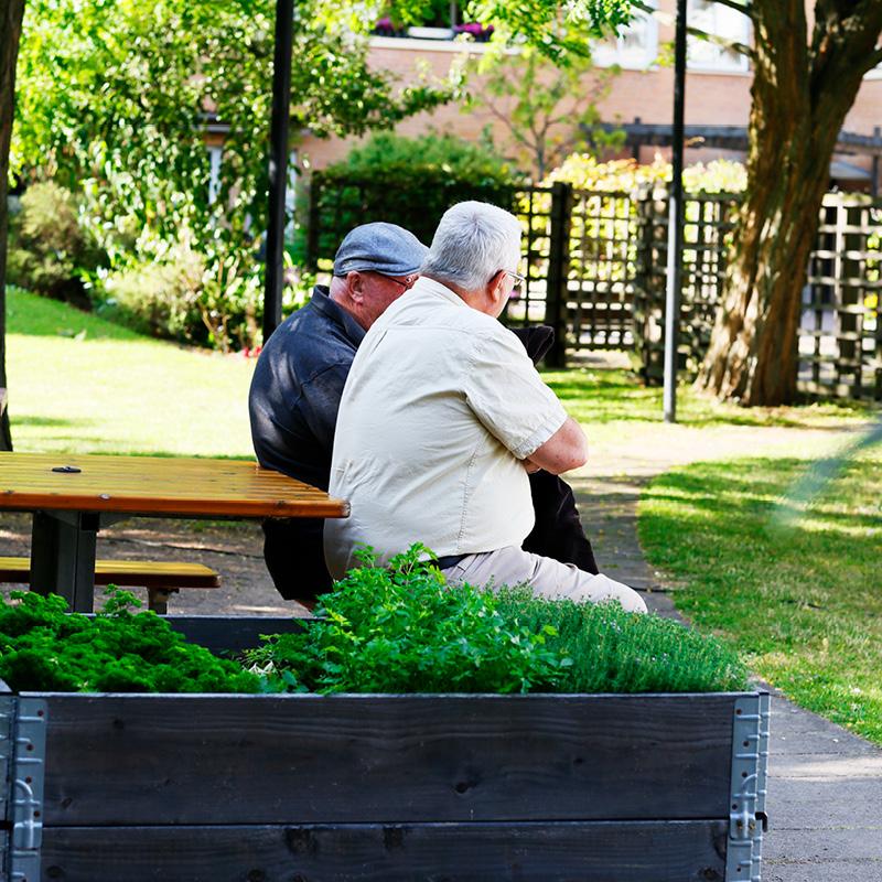 Två män sitter och pratar på gården.