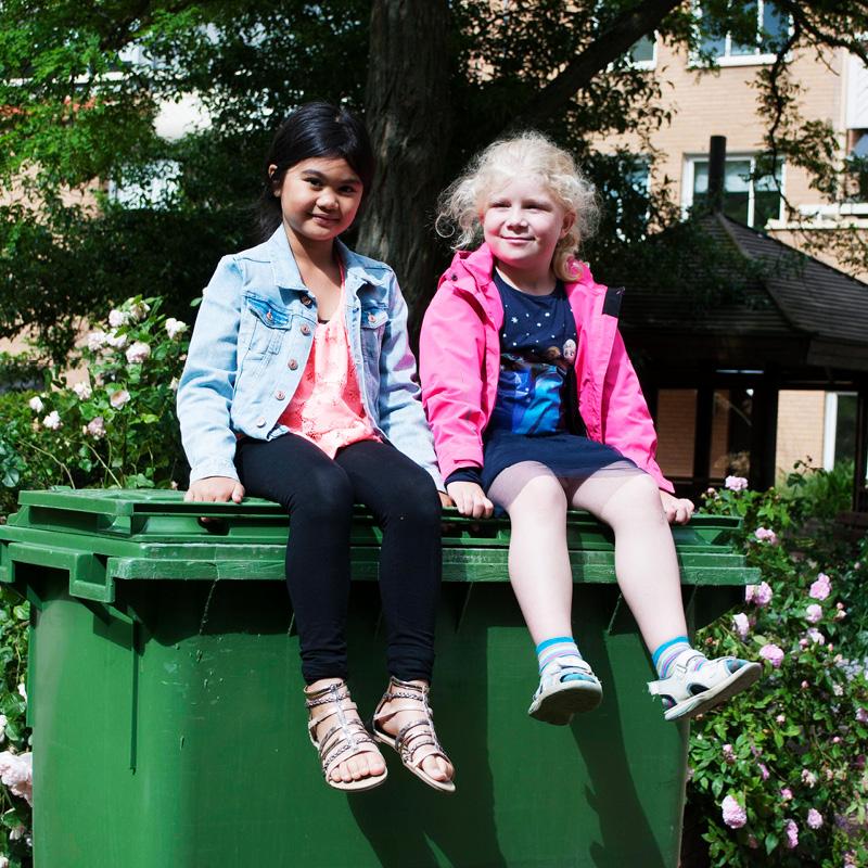 Två flickor sitter på ett sorteringskärl.