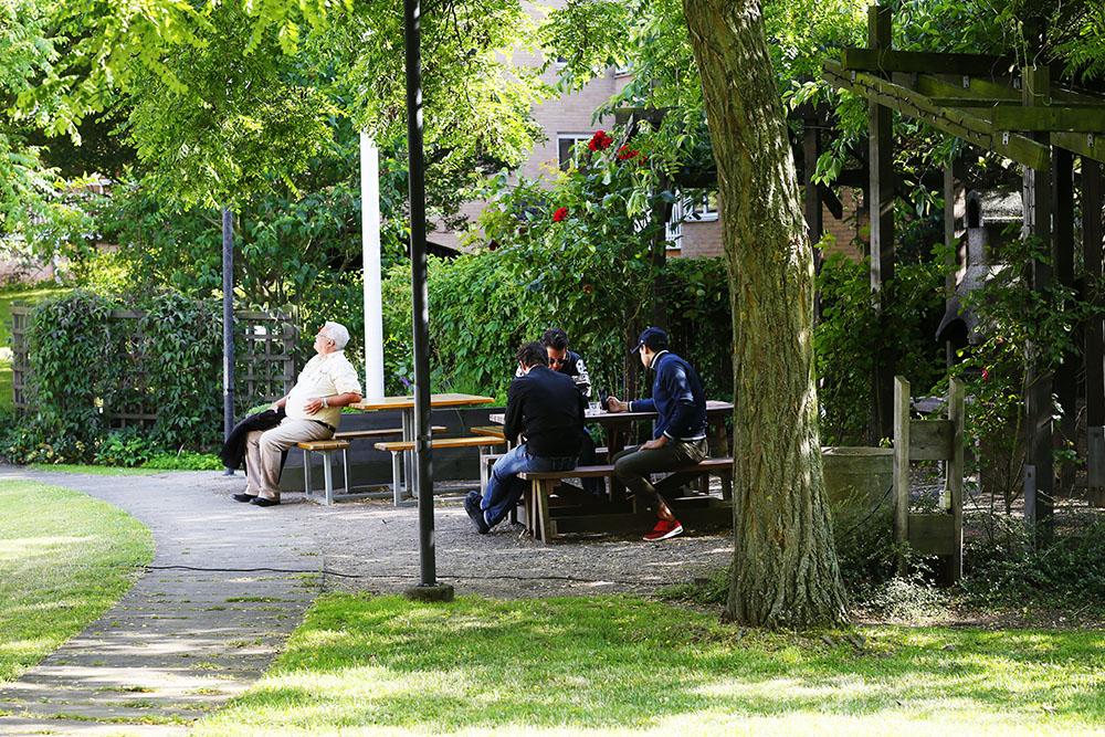 Några sitter på bänkar i trädgården.